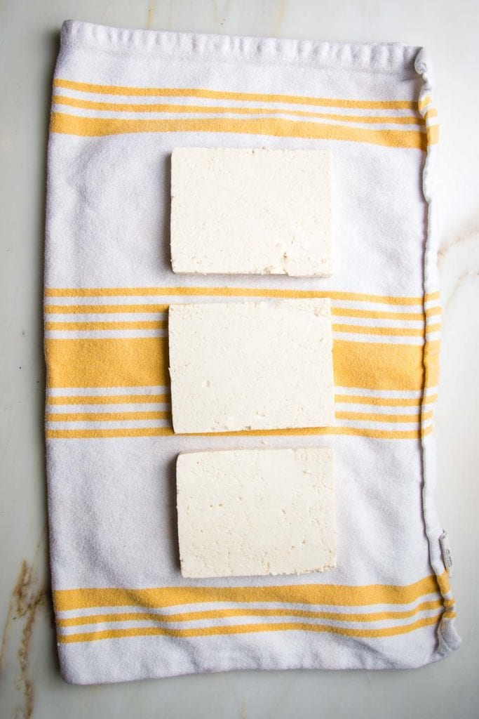 White dish towel with yellow stripes. Three thin slabs of tofu layed out in single layers.
