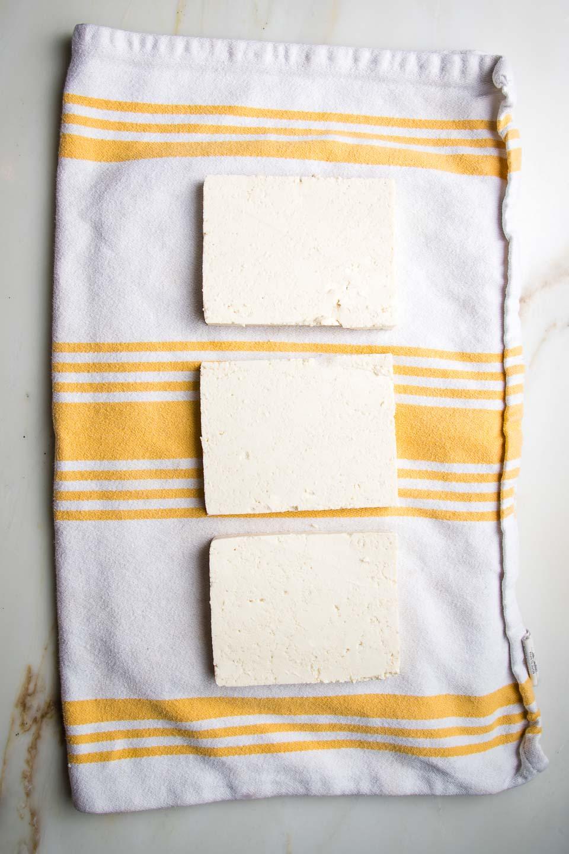 Slabs of tofu on a yellow striped tea towel.