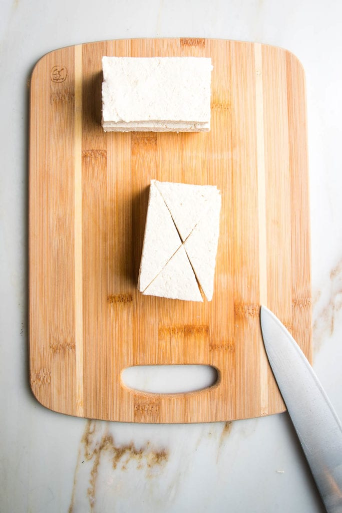 Wooden cutting board with stacks of pressed tofu and a knife, cutting them into small triangles.