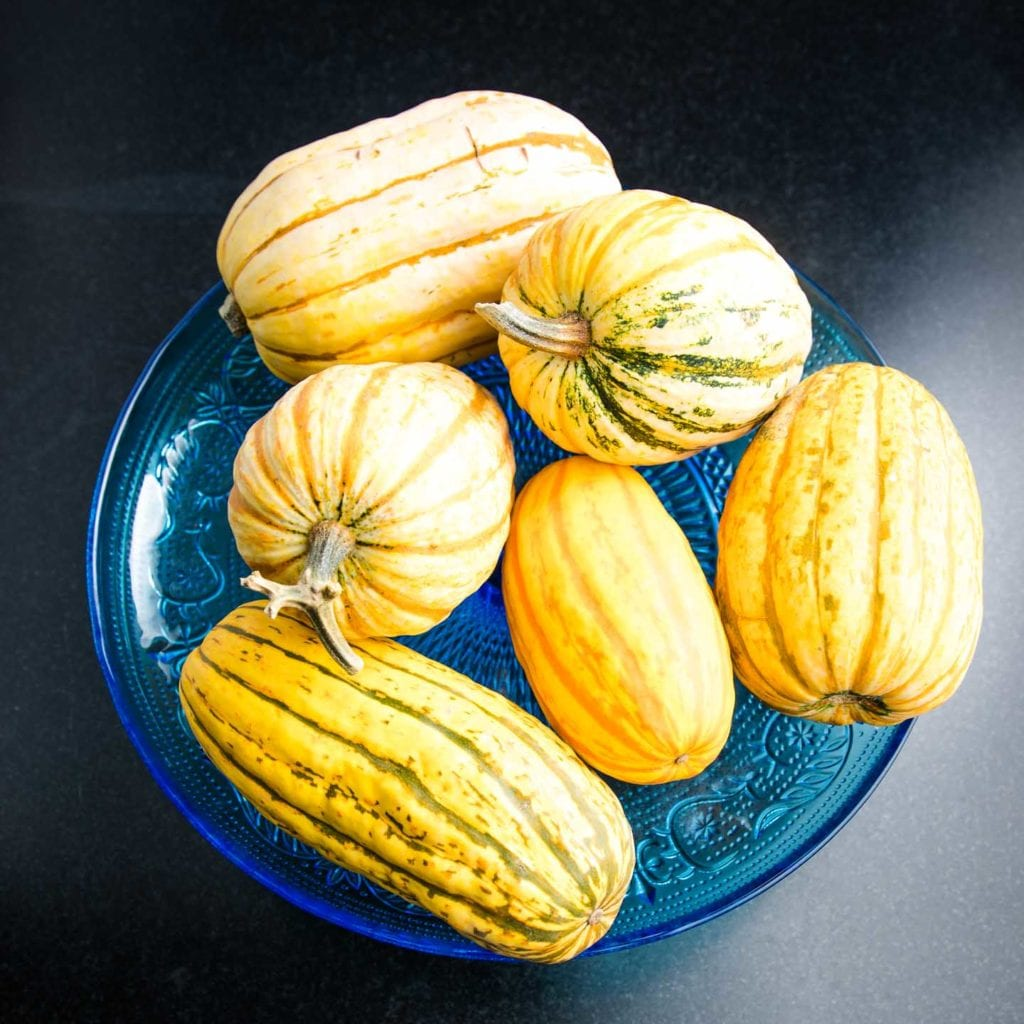 Blue glass pedestal filled with different shapes and sizes of delicata squash.
