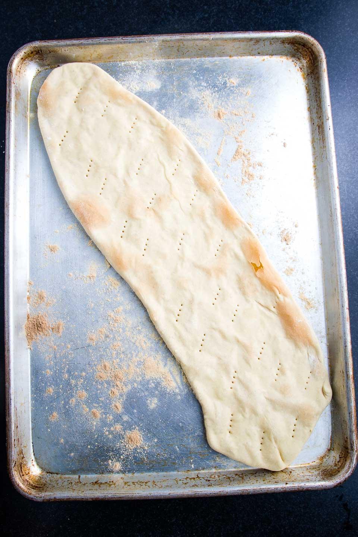 Crispy flatbread pizza crust on a rimmed baking tray.
