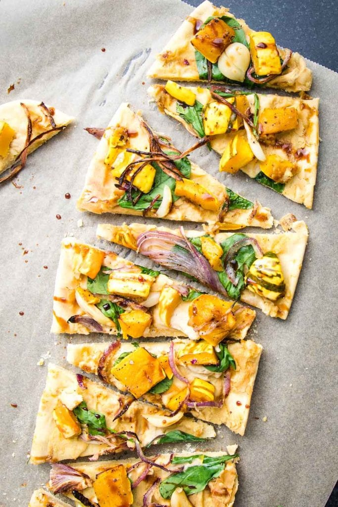 Unbleached parchment paper with a long flatbread vegan pizza, loaded with hummus, spinach and roasted squash, caramelized onions and roasted garlic.