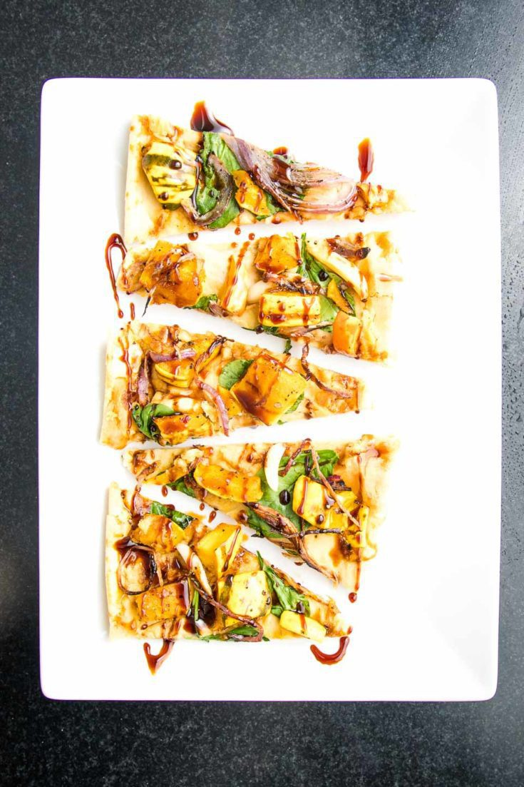 Small triangle appetizer flatbread pizza slices loaded with hummus, spinach, roasted squash, onions and garlic with a date syrup drizzle