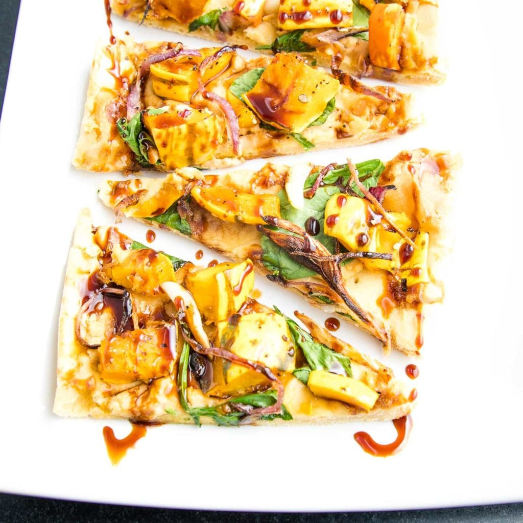 Appetizer sized portions of flatbread topped with roasted squash, onions and garlic and drizzled with date syrup.