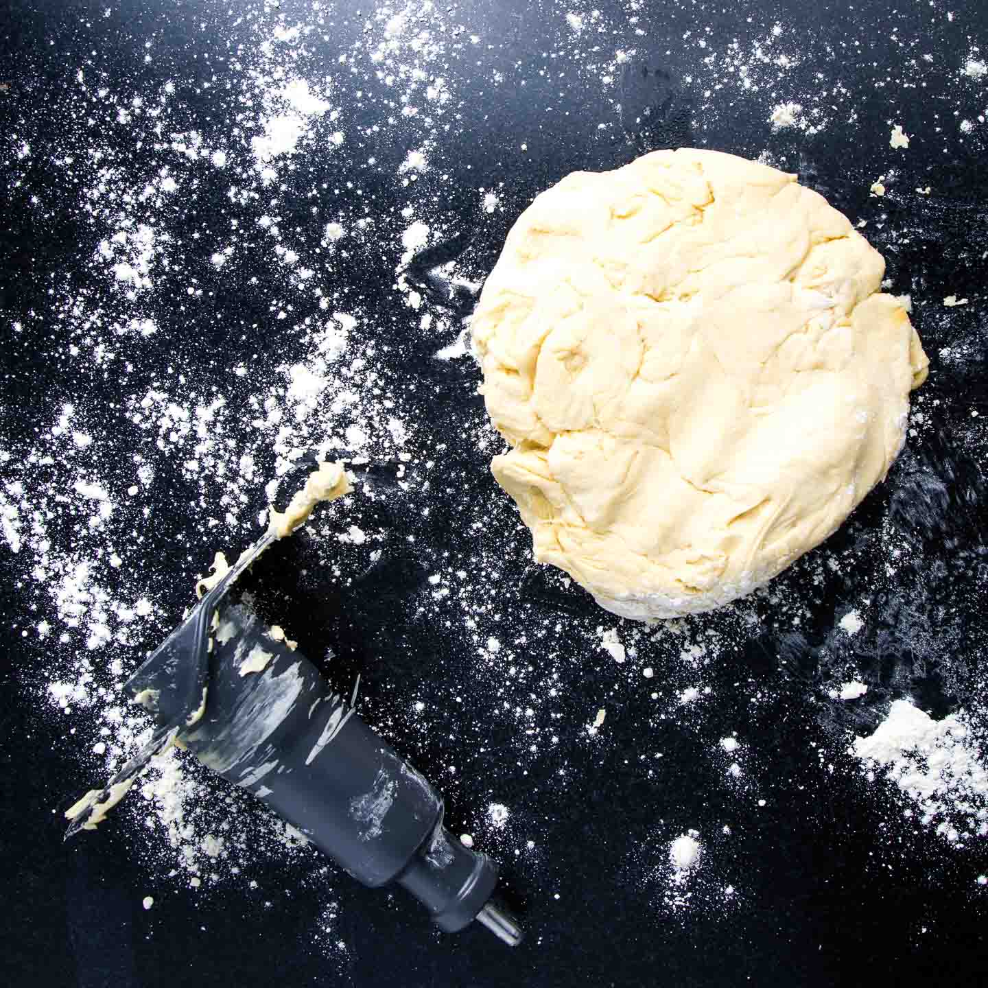 Ball of dough on a black surface sprinkled with flour and the food processor blade.