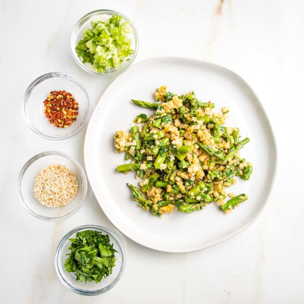 Cauliflower rice with asparagus on a rimmed white plate, surrounded on the left with small glass dishes with sliced scallions, crushed red pepper, sesame seeds and chopped fresh parsley