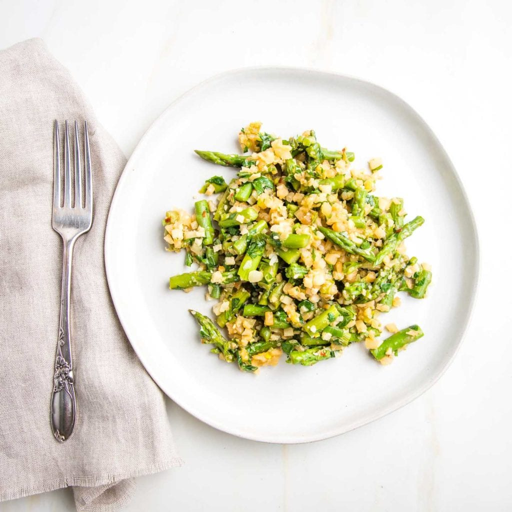 White rimmed plate with cauliflower rice and asparagus in the center.  A neutral linen napkin with silver fork on the left.