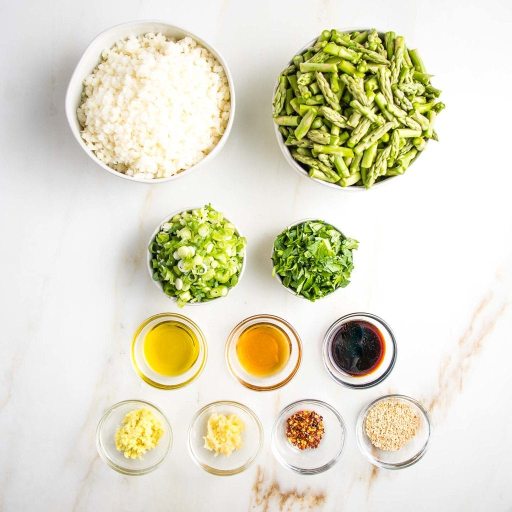 """Ingredients lined up in small glass dishes or white bowls: riced cauliflower, 1"""" pieces of asparagus, sliced scallions, chopped parsley, olive oil, toasted sesame oil. tamari, grated ginger, grated garlic, crushed red pepper and sesame seeds"""