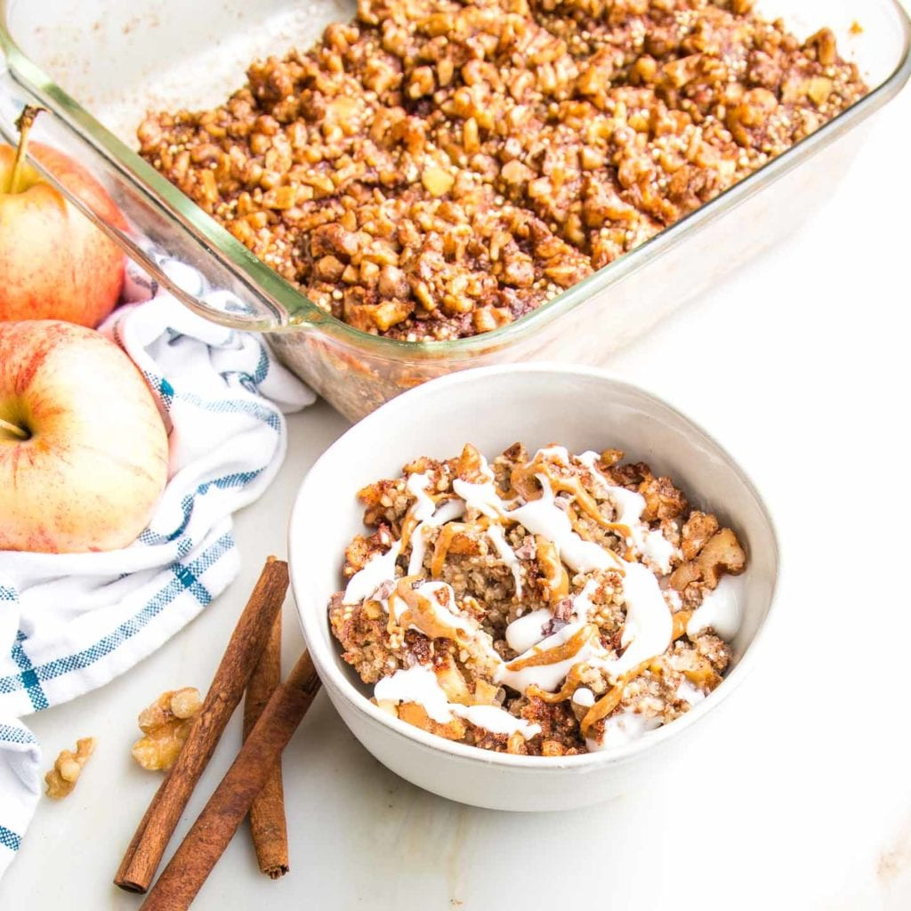 baking dish with quinoa bake, topped with walnuts, with apples and cinnamon sticks on a blue wide check tea towel and in the foreground a small bowl filled with breakfast bake that is topped with vegan yogurt and a swirl of almond butter.