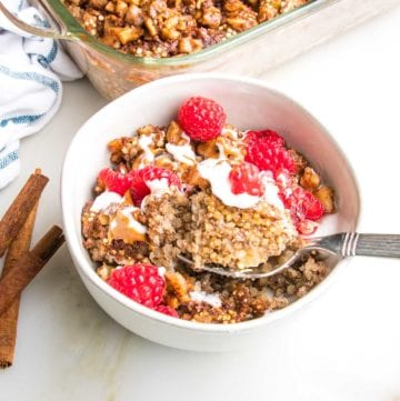 Bowl with quinoa breakfast bake, topped with yogurt and almond butter. Sprinkled with chopped walnuts and fresh raspberries