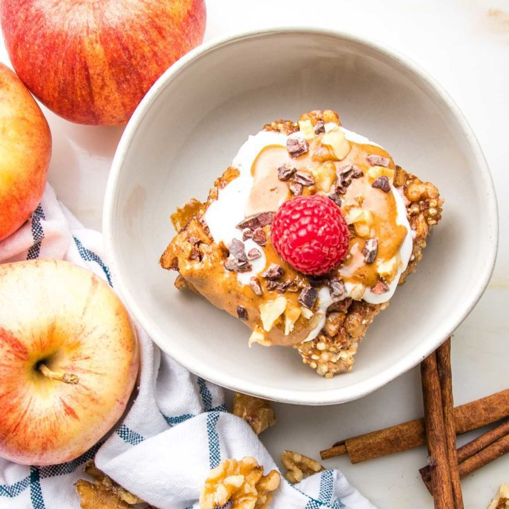 White bowl with a slice of quinoa breakfast bake with a dollop of almond yogurt and drizzled with almond butter, sprinkled with chopped walnuts and cacao nibs, topped with a red raspberry. Whole apples and cinnamon stick surround the bowl.