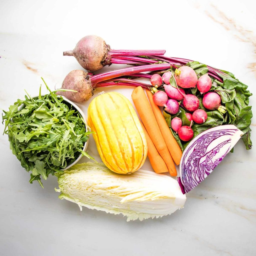 Ingredients for rainbow salad before chopping:  small bowl of arugula, 1/4 green cabbage, 1/4 purple cabbage, delicata squash, 2 red beets with greens, radishes, 3 peeled carrots.