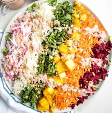 Shredded rainbow salad on a round rimmed white plate: a layer of arugula covered with shredded radish, green cabbage, beet leaves, roasted delicata squash, shredded carrots, purple cabbage and red beets.