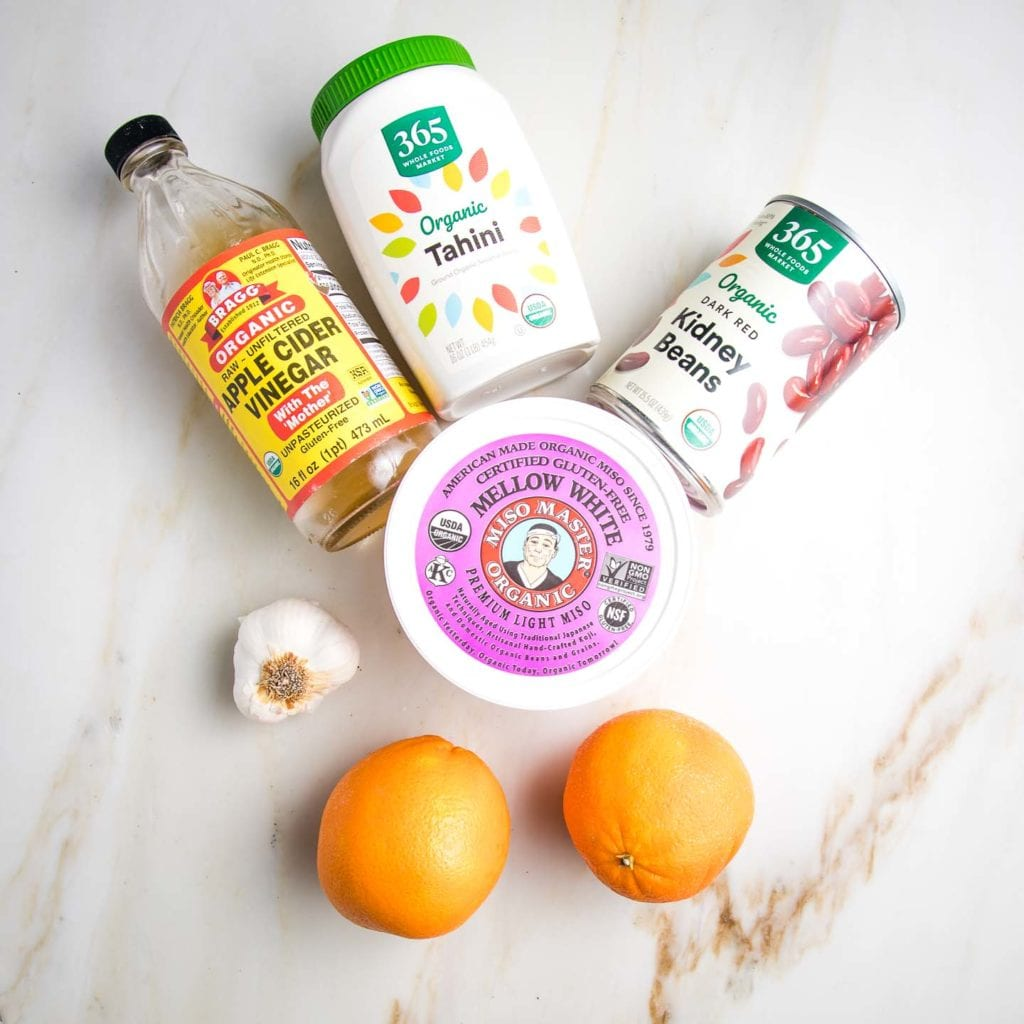 Salad Dressing Ingredients on a marble counter: bottle of apple cider vinegar, head of garlic, 2 oranges, jar of tahini, can of red kidney beans, container of light miso paste.