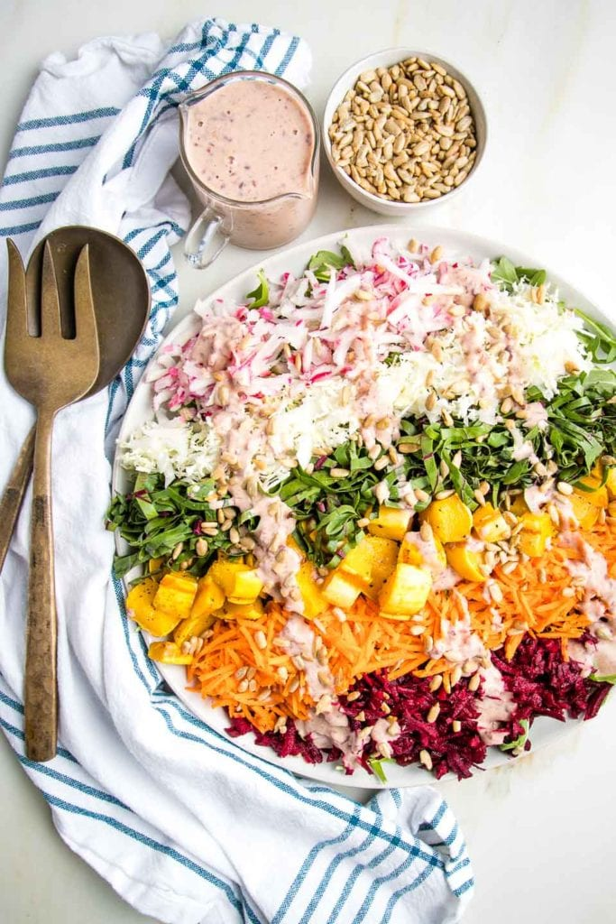 Shredded Rainbow Salad: radishes, cabbage,  beet greens, carrots, red beets and roasted delicata squash cubes on a white rimmed plate, plus a small cut of pink dressing and a bowl of sunflower seeds.