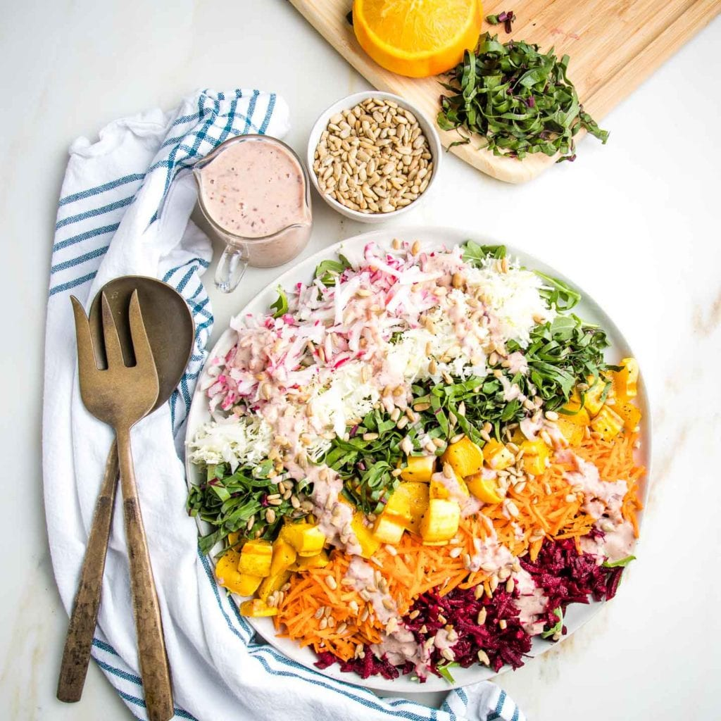 Rainbow salad on a white plate with a pink dressing drizzled across the colorful stripes. Serving pieces on a white tea towel with blue stripes, a small pitcher of extra dressing plus some sunflower seeds and a background cutting board with julienned beet greens and some oranges that have already been squeezed.