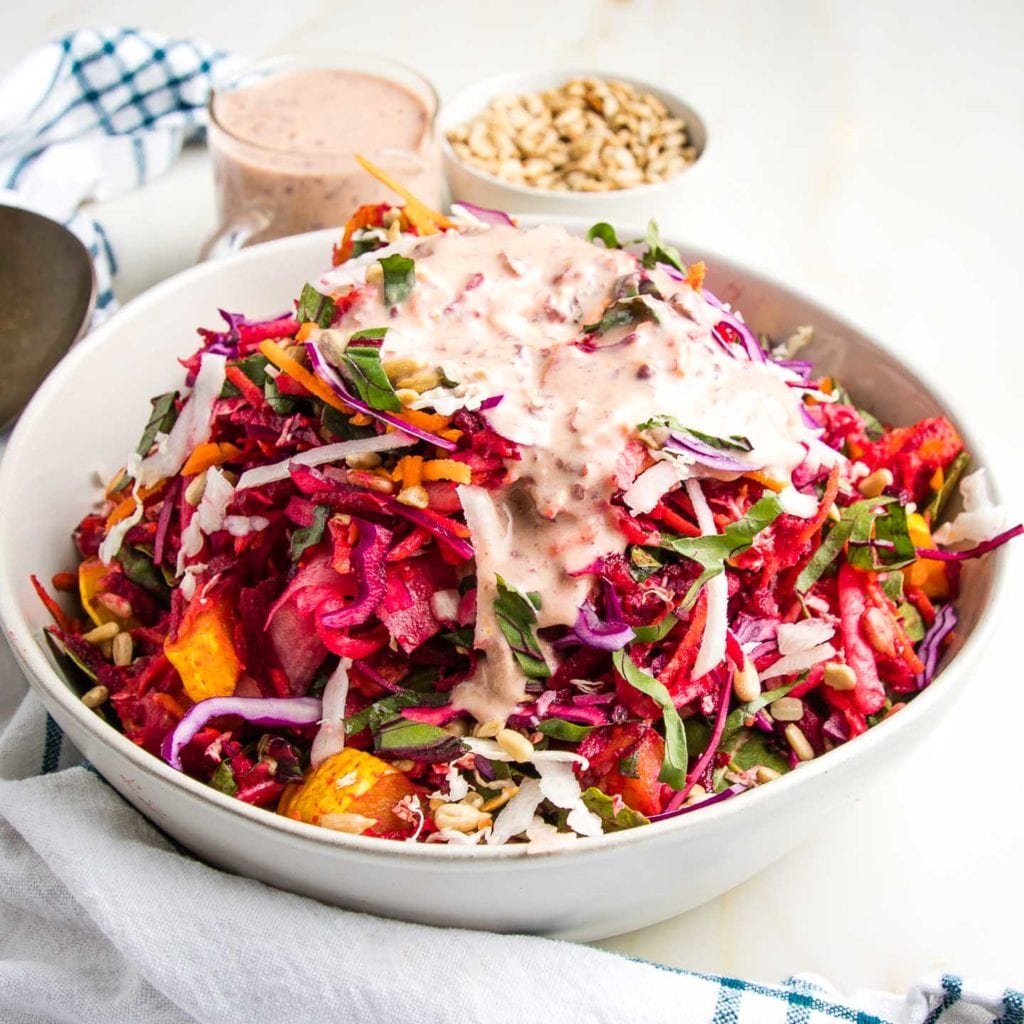 Vibrant tossed colorful salad with pink dressing on top.