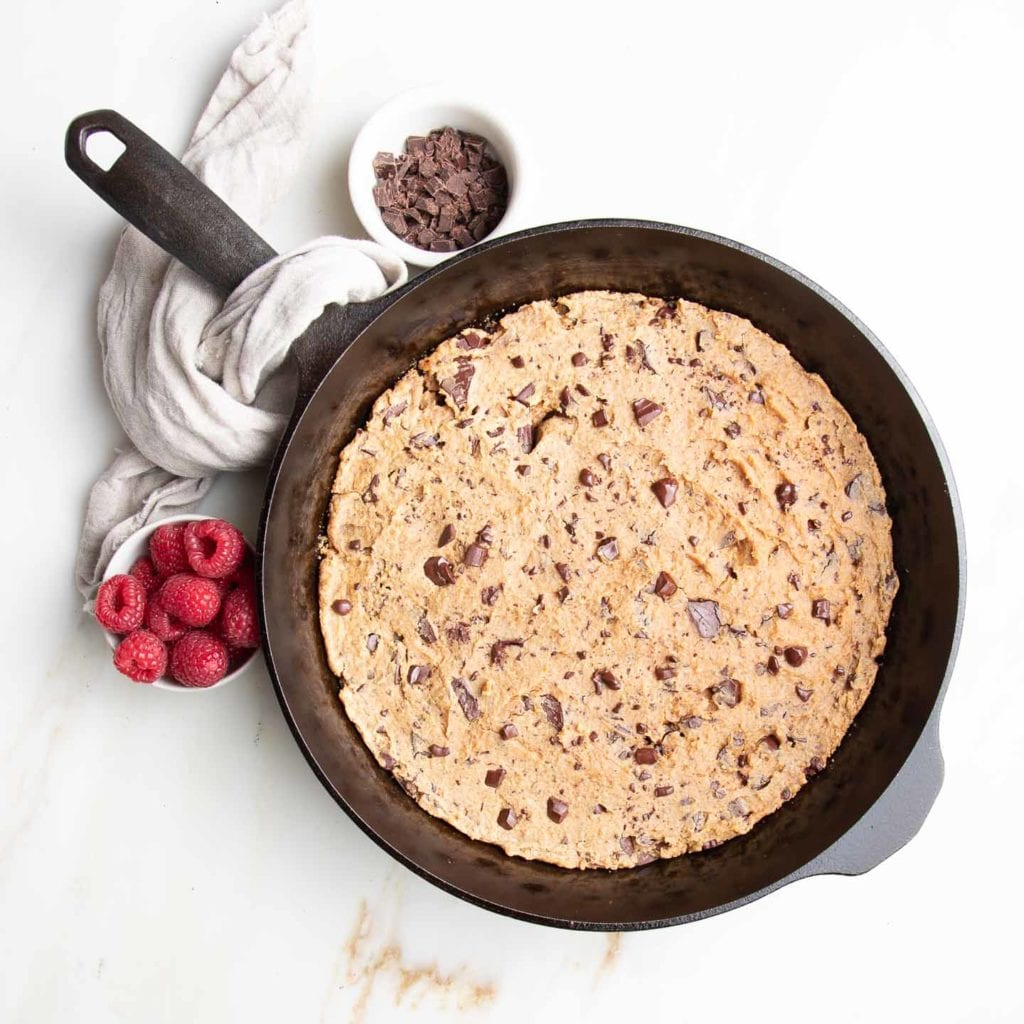 Cast iron skillet with chocolate chunk cookie inside.  Linen napkin draped over handle of pan and small dish of red raspberries on one side of handle, chocolate chunks on the other side in a small white dish.