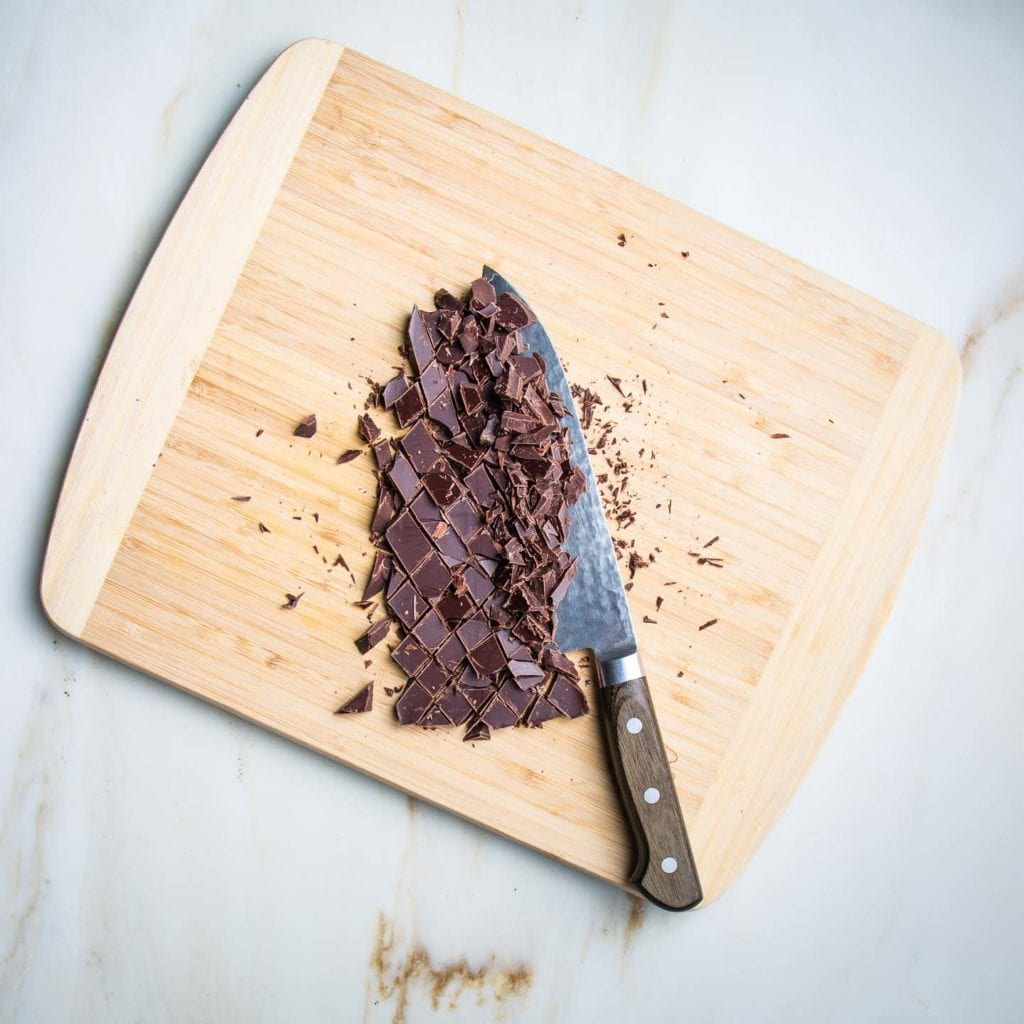 Bamboo cutting board with a bar of dark chocolate cut into chunks with a chef's knife.
