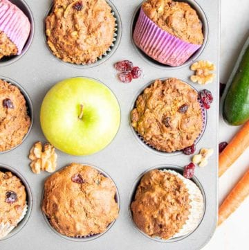 Muffin tin filled with morning glory muffins, one has a green apple, there are dried cranberries and walnuts strewn about and zucchini and carrots off to the side