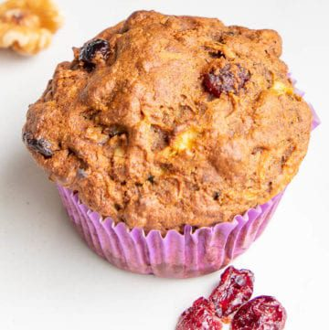 close up of a morning glory muffin, in a purple cupcake wrapper, with cranberries and walnuts surrounding it.
