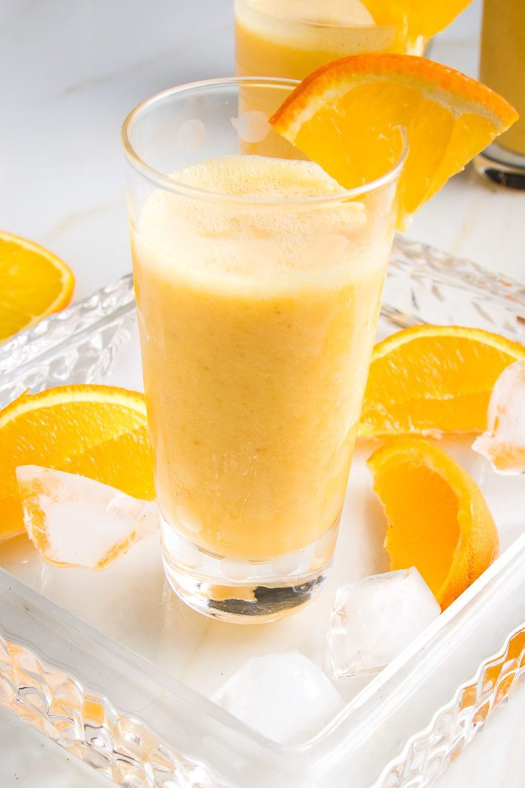 Glass filled with a frothy Orange Smoothie, with a wedge of orange on the side of the glass, more orange wedges on the glass serving tray along with some ice cubes.