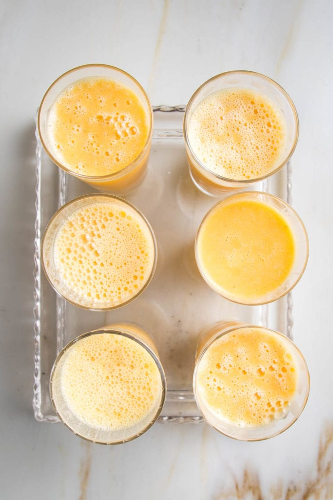 6 glasses filled with orange julius smoothies on a glass serving tray.