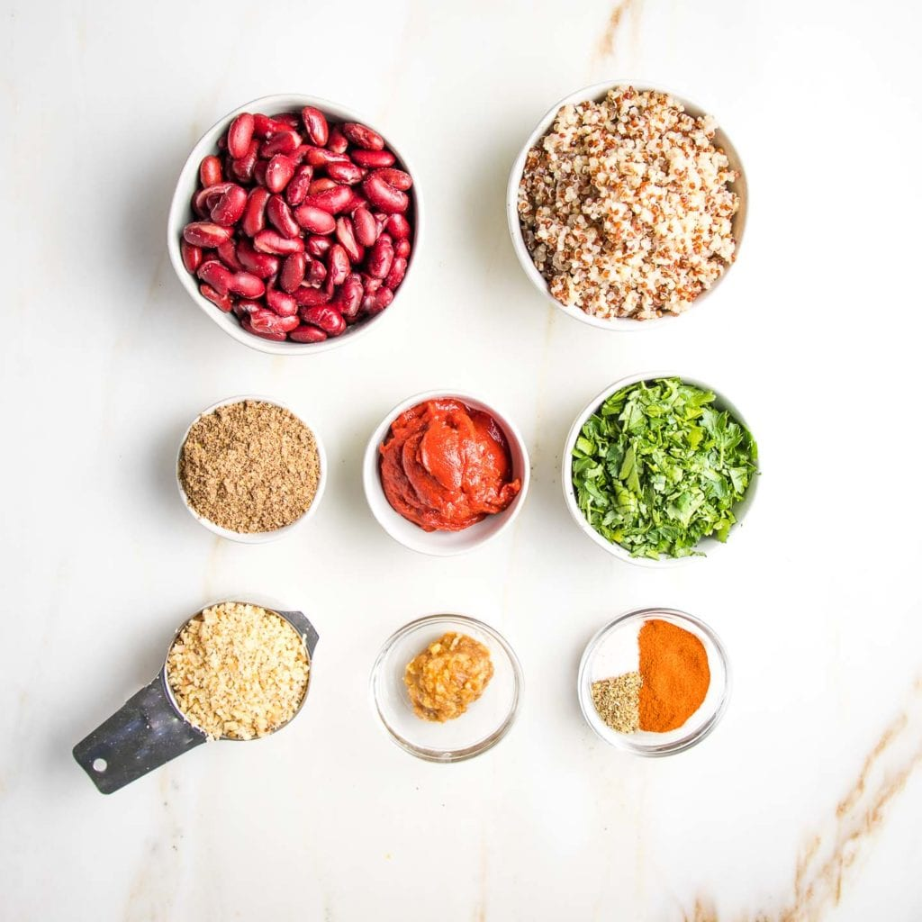 Ingredients for quinoa burgers: kidney beans, quinoa, ground flax, tomato paste, fresh parsley, chopped nuts, miso and spices.