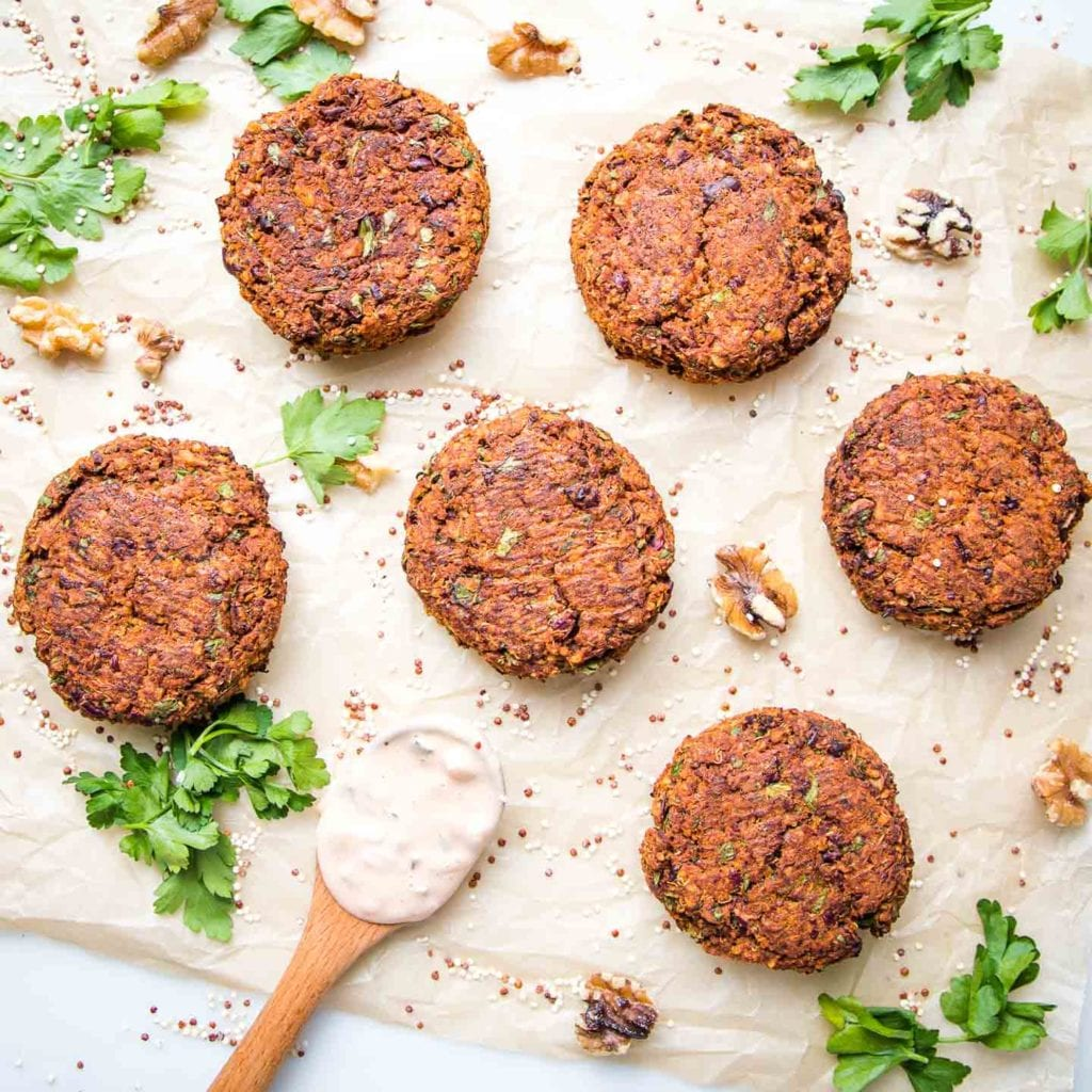 Quinoa veggie burger patties on a sheet of unbleached parchment paper, scattered with quinoa, fresh parsley, walnuts and a small wooden spoon filled with russian dressing