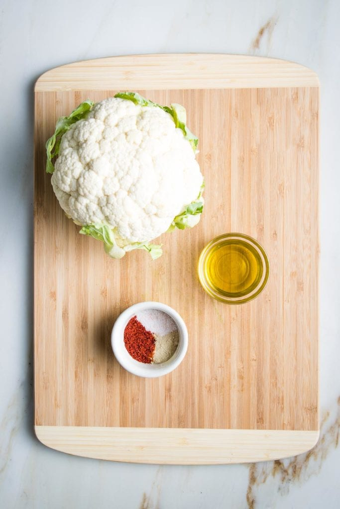 Wooden cutting board with a head of cauliflower, a small glass dish with olive oil and a small white dish with paprika, salt and white pepper