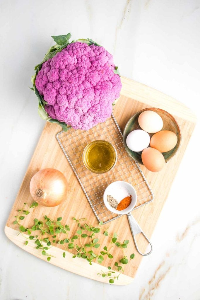 Cauliflower kugel recipe ingredients on a cutting board:  large head purple cauliflower, small ceramic dish with 4 eggs of varying colors from white to brown, sprigs of fresh oregano, small white dish with spices, small glass bowl of olive oil, a yellow onion and a potato shredder.