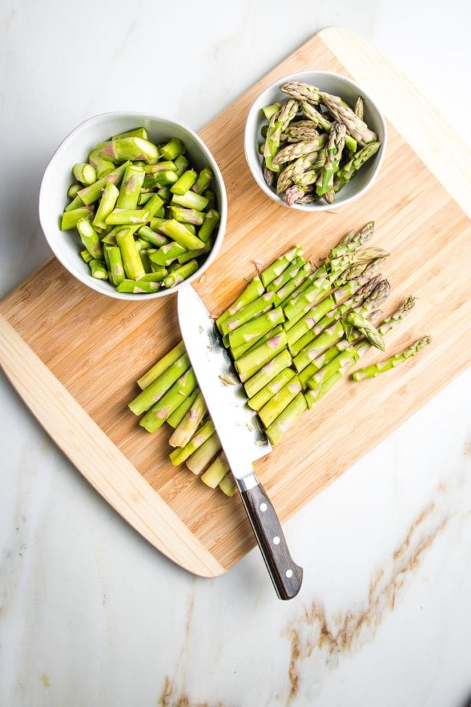 bamboo cutting board with a bunch of asparagus cut into 1-inch pieces with a chef's knife.  Two bowls separate those cut.  As maller bowl has the tips and a slightly larger white bowl holds the other pieces from the bottom of the spears.