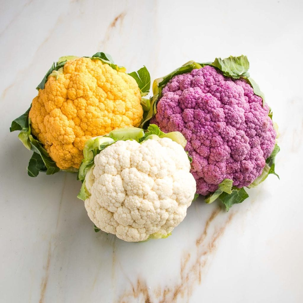 Three heads of cauliflower: purple, white, and yellow.  All have their green leaves attached.