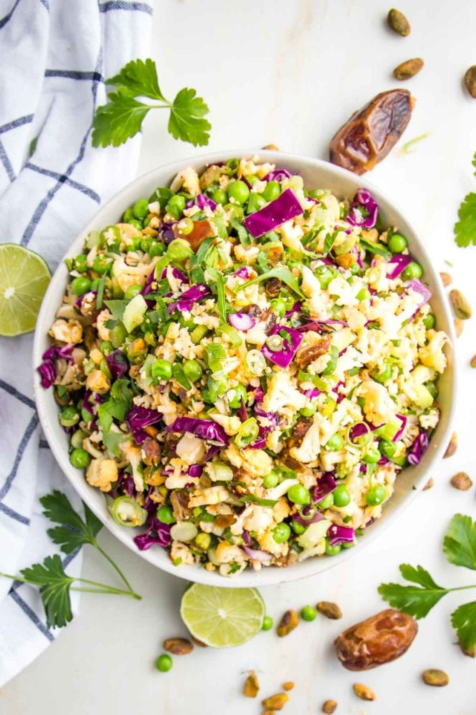 Large white bowl, filled with chopped colorful salad that includes purple cabbage, scallions, shaved cauliflower, fresh parsley, sliced scallions, green peas, diced dates. There are fresh limes, dates, fresh parsley and a dish towel strewn around the salad bowl.