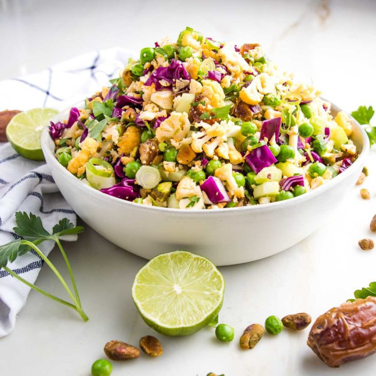 Side view of a white bowl that is filled with a colorful chopped salad that includes purple cabbage, yellow cauliflower, pistachios, fresh parsley, sliced scallions, green peas. Strewn around on the counter are fresh lime slices, dates, fresh parsley and a dish towel.