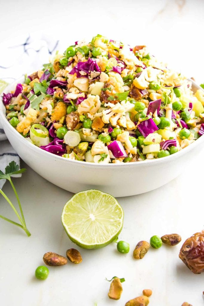 White bowl filled with colorful chopped salad that includes purple cabbage, fresh parsley, green peas, yellow cauliflower, pistachios, chopped dates, and scallions. There is a fresh slice of lime, some pistachios, dates and fresh parsley in the foreground on the white countertop
