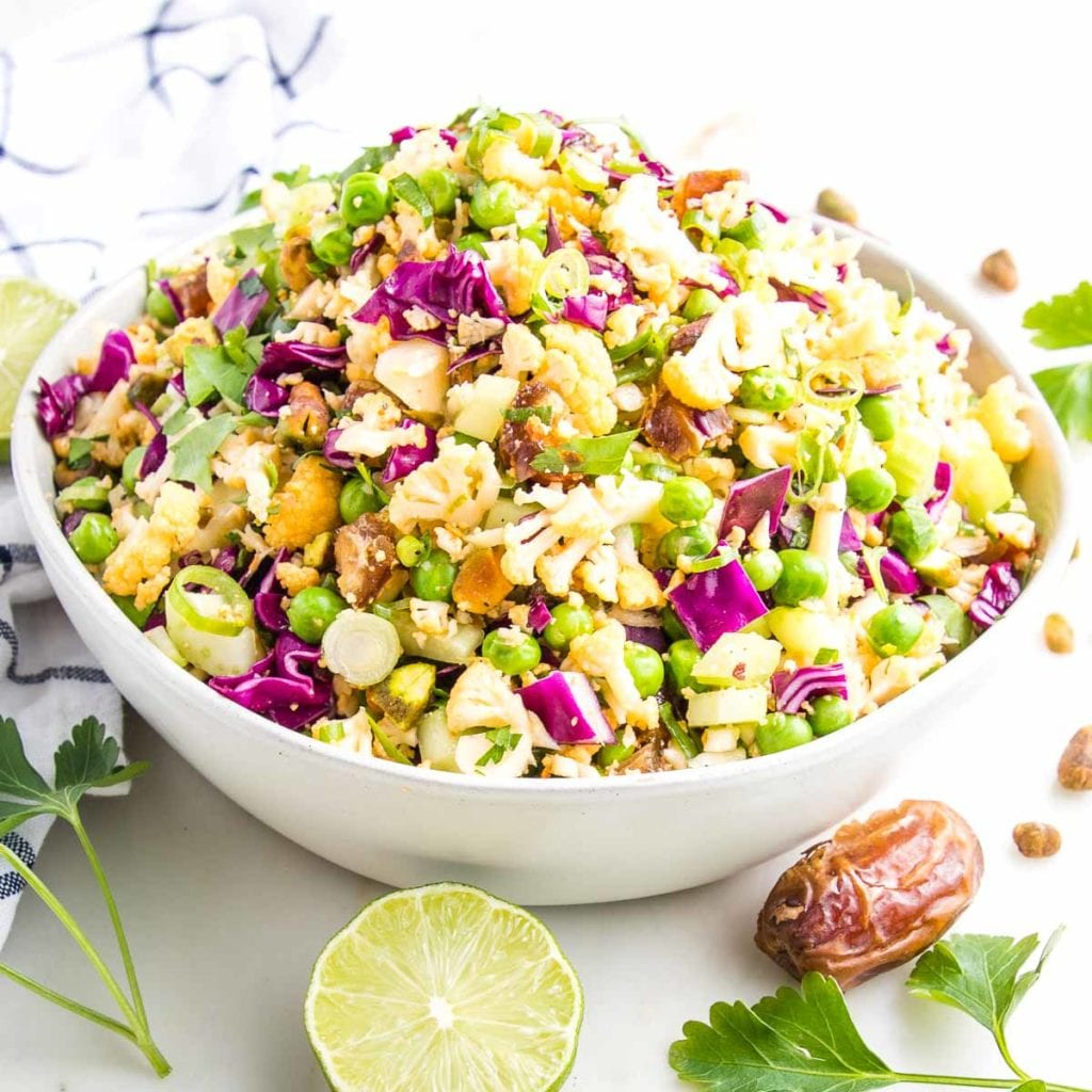Colorful raw cauliflower chopped salad in a white bowl.  THere is a lime, some dates, pistachios and fresh parsley in the foreground along with a dish towel.