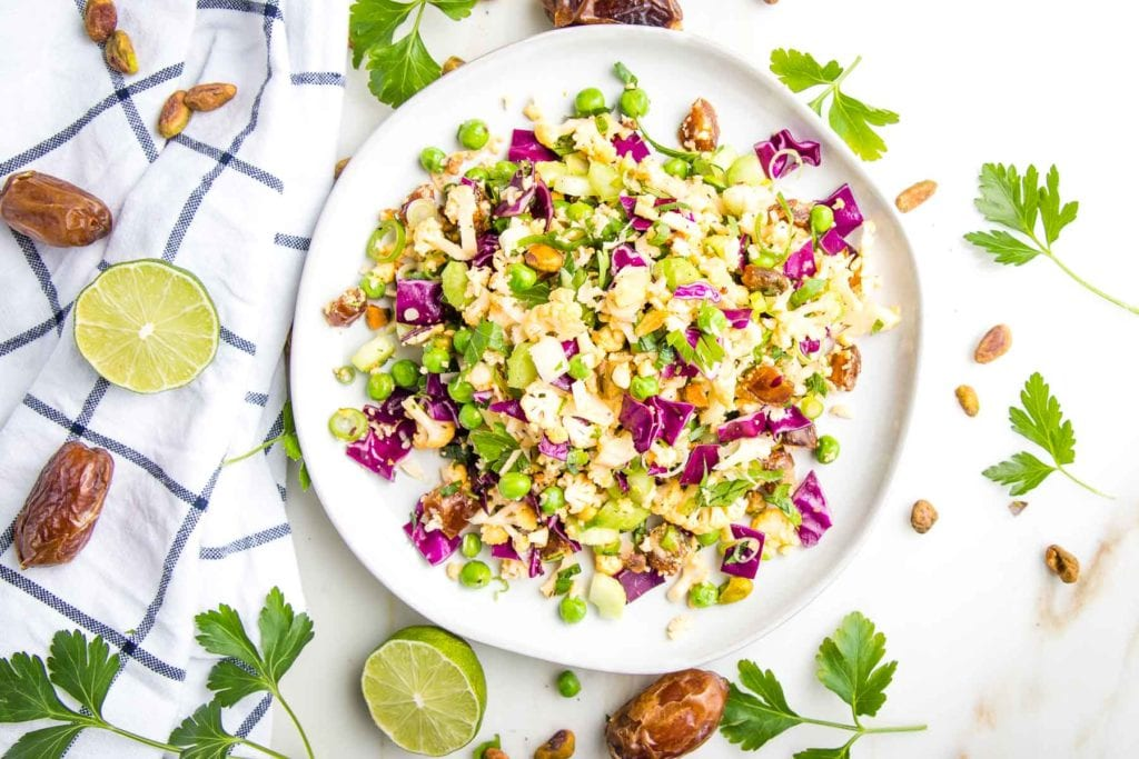 white rimmed plate with colorful chopped salad, on the side is a dish towel with fresh lime, dates, fresh parsley and some additional pistachios and herbs strewn about on the white countertop.