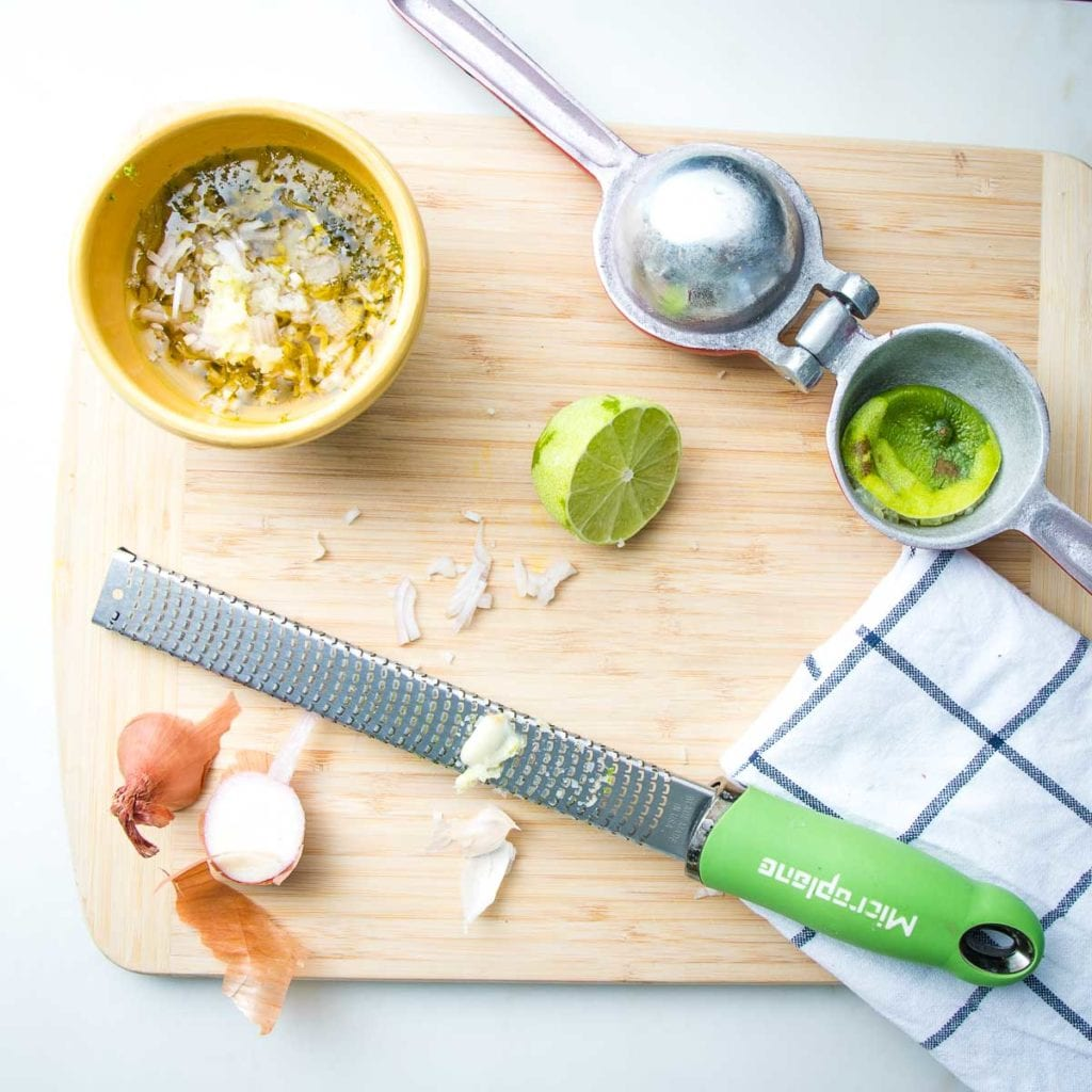 Small yellow bowl with lime vinaigrette. Also on the cutting board, are the ends of a shallot, a microplane zester with an end of a garlic clove and a juice squeezer with a squished lime inside. Plus a dish towel.