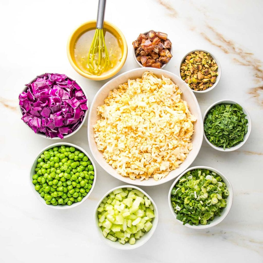 Bowls of ingredients for raw cauliflower salad. chopped cabbage, green peas, diced celery, sliced scallions, chopped parsley, pistachios, diced dates and a lime vinaigrette. All small bowls positioned in a circle, surrounding a white bowl of shaved cauliflower.