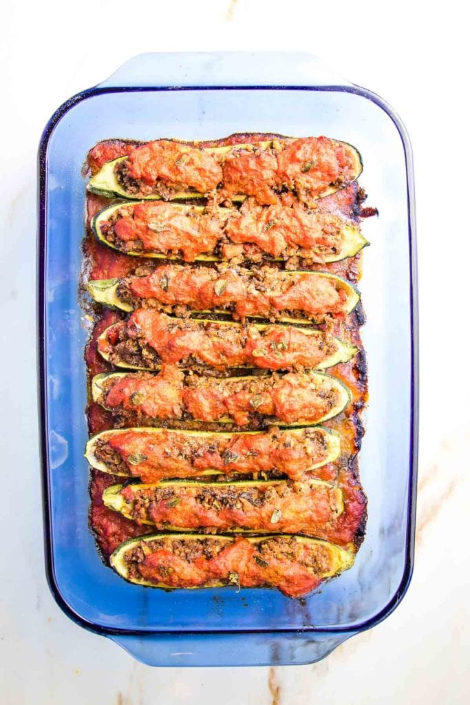 Baked stuffed zucchini boats in a casserole dish.