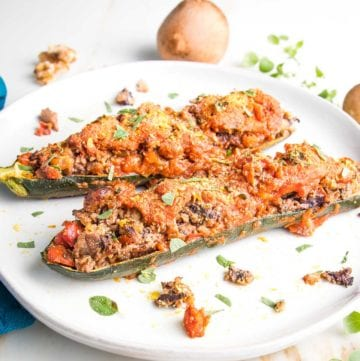 Rimmed white plate with 2 zucchini boats, stuffed with mushrooms and other chopped veggies, topped with tomato sauce and fresh herbs.