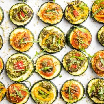 Rows of zucchini slices, topped with red or green sauce and various vegetable toppings to create mini pizzas. All are sprinkled with vegan parmesan and fresh basil.