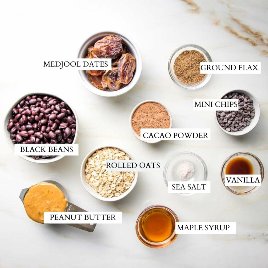Images of small bowls of ingredients that are labeled: black beans, medjool dates, ground flax, cacao powder, rolled oats, peanut butter, maple syrup, mini chocolate chips, vanilla and sea salt