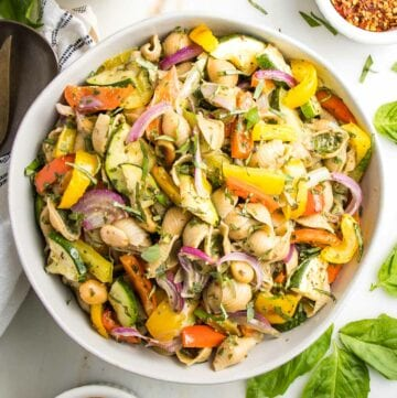 Large white bowl with vegetable pesto pasta salad. Colorful yellow and red peppers, purple onions and zucchini are roasted, there are fresh herbs sprinkled on top and a small dish of crushed red pepper on the side.