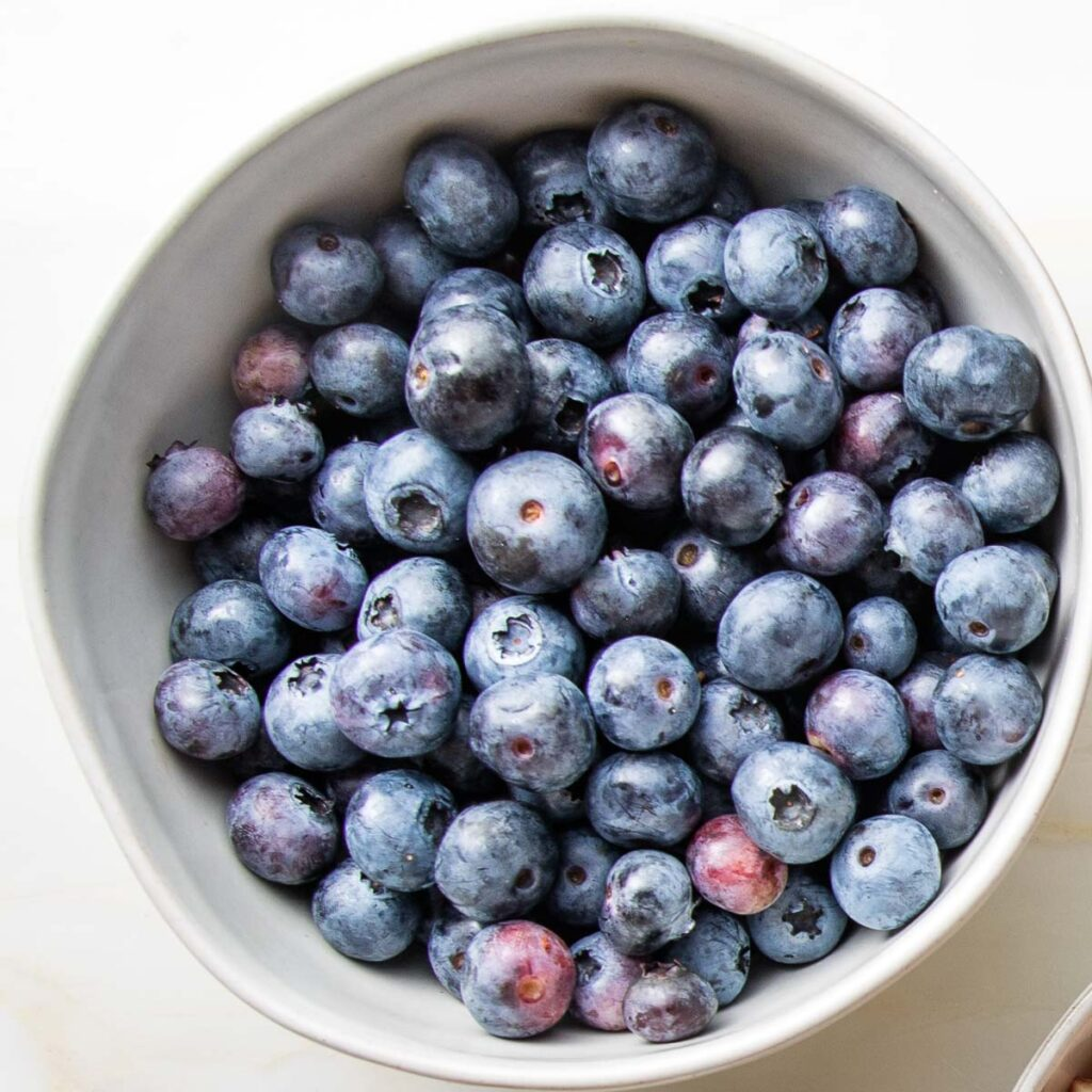 Close up of a white bowl filled with blueberries
