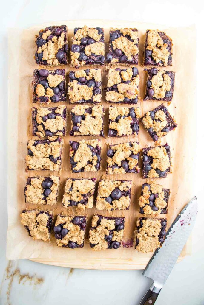 24 squares of blueberry bars on a cutting board with the knife on the bottom right corner of cutting board.