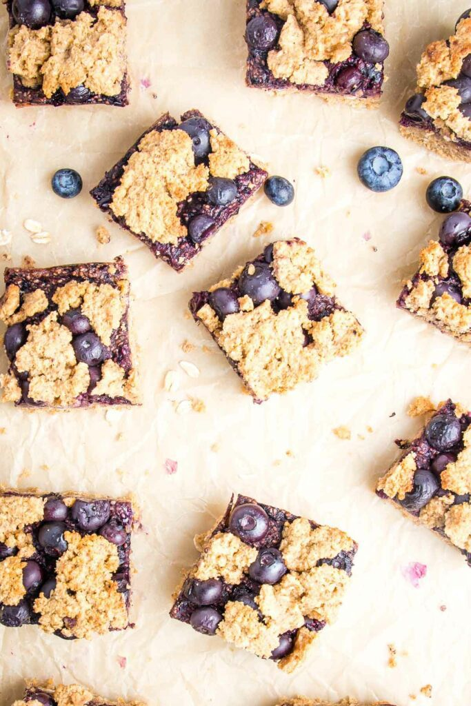 Blueberry Crumb Bars cut into squares on a piece of parchment paper with a few fresh blueberries sprinkled about.