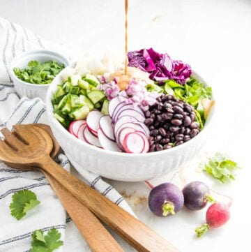 White bowl with sections of black beans, sliced radish, diced cucumbers, chopped cabbage, cubed jicama all on a bed of romaine. Orange chipotle dressing is being poured over the bowl in the center. Wooden serving pieces on a white dish towel striped in navy are on the side along with three whole radishes.