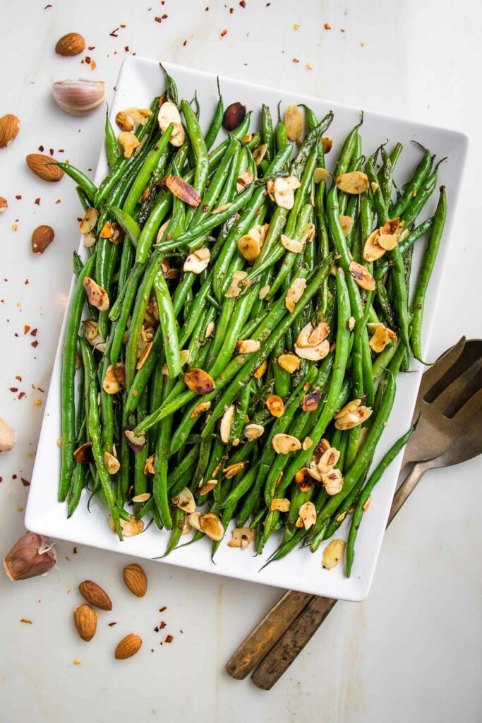 White rectangular plate loaded with bright green beans, toasted almonds. There are cloves of garlic, sliced almonds and crushed red pepper strewn around the plate and a bronze colored large spoon and fork on the right side.